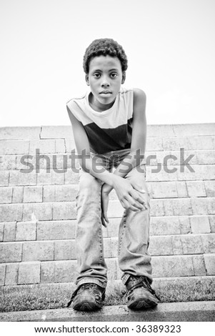 a boy standing in front of a wall - stock photo