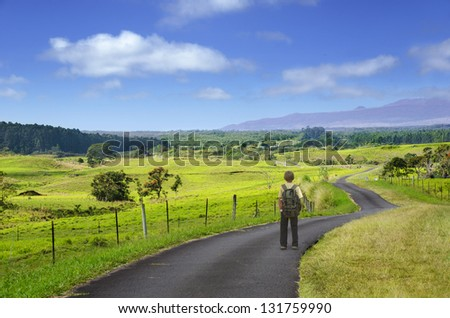 A boy standing on a long and winding country road. - stock photo