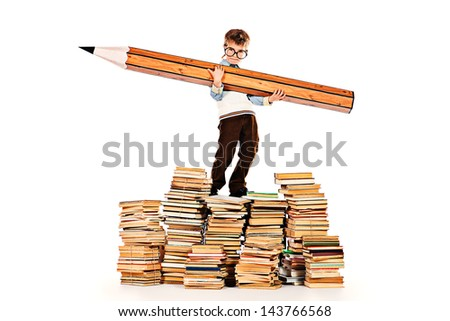 A boy standing on a pile of books and holding a huge pencil. Education. Isolated over white. - stock photo