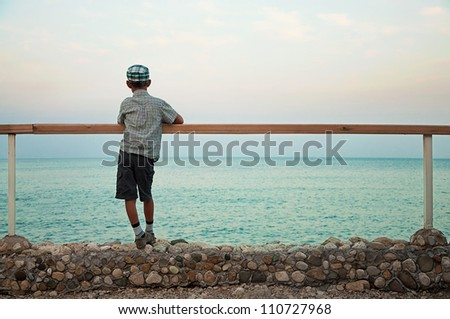 a boy standing on quay in the evening during sunset looking at sea