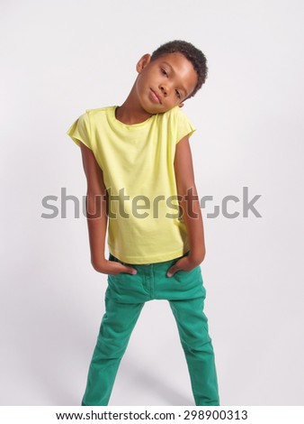 A boy standing with hands in the pockets over grey background. Vertical Shot.