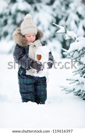 A boy stands in the snow. A child in a winter forest.