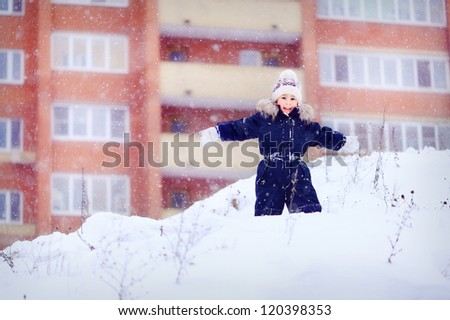 A boy stands on a snowy mountain. Hand in hand. Winter and cold. A child playing outdoors. In the background the high house. Happy baby.
