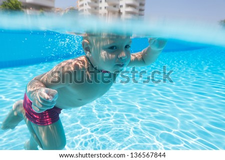 A boy swimming under water in the pool of hotel - stock photo