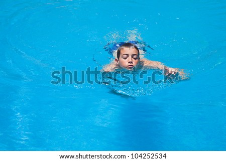 a boy swims in a pool