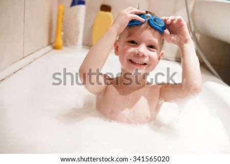 A boy swims in the bathtub at their home in swimming goggles. - stock photo