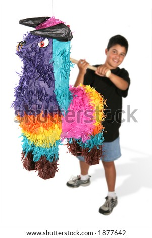 A boy swinging his bat at a bull shaped pinata - stock photo