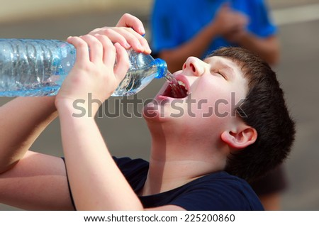 A boy thirsty eagerly drinking water from plastic bottle - stock photo
