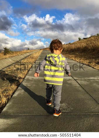 A boy toddler is energetically walking up the hill on a path after a rain storm passed.