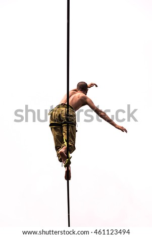 A boy walking on a Slackline/View from below of a guy who practices balancing on tightwire