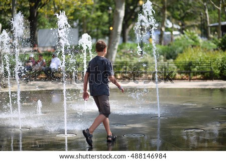 A boy walks on the fountain in the park, view from the back