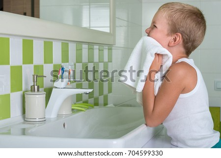 A boy washes his face, wipes her face with a towel in the bathroom.
