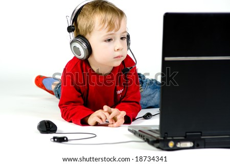 A boy watching a movie or listening to music on a laptop.