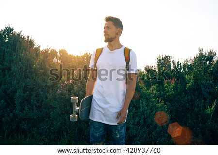 A boy wearing a blank white t-shirt is standing with his skateboard. A man with a backpack is looking aside on a greeny background. Flare light.