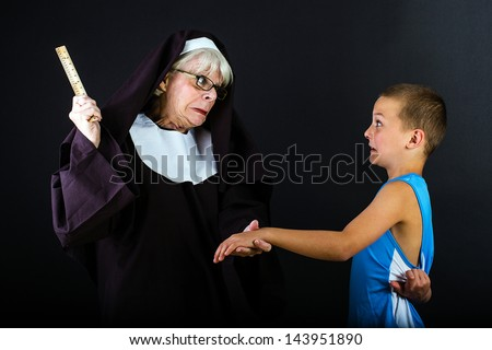 A boy with a fearful expression as a nun is about to hit him with a ruler - stock photo