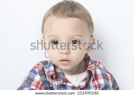 A boy with a hearing aids on gray background - stock photo
