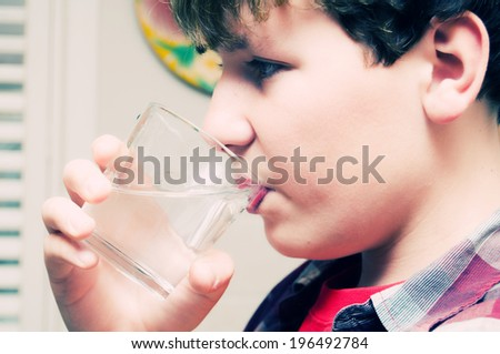 A boy with dark hair drinking a glass of water.
