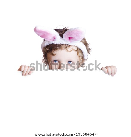 A boy with Easter bunny ears holding a white blank board