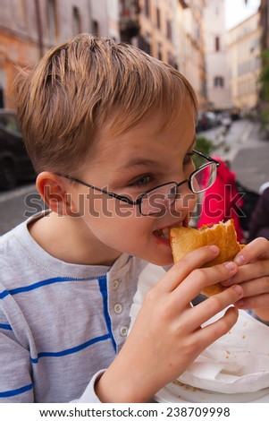 A boy with glasses having a meal. Rome, Italy