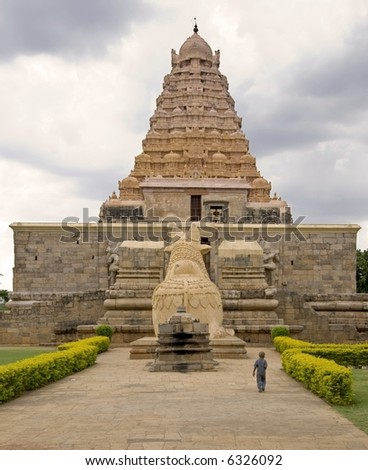 A boy with shaved head walking towards the  majestic temple (Gongaikonda Cholapuram, circa 12th century)