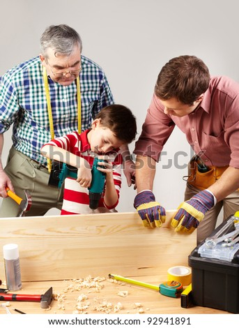 A boy working with drill under his father and grandpa?s supervision - stock photo