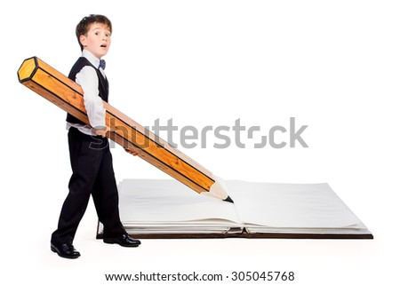 A boy writes with a big pencil in a big book. Educational concept. Isolated over white. - stock photo
