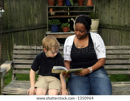 A boys babysitter reading him a story. - stock photo
