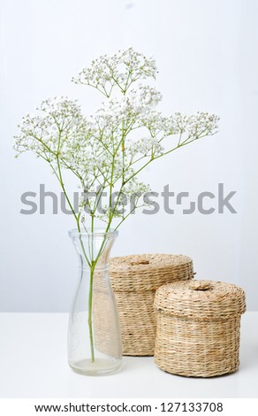 A branch of flowers in a small vase and two closed baskets on a white table - stock photo
