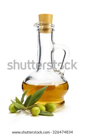 A branch of olive and olive oil in a decanter on a white background