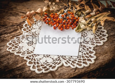 A branch of rowanberry with dry red berries on hand made napkin on wooden table. Autumn background with copy space. crocheted doily - stock photo
