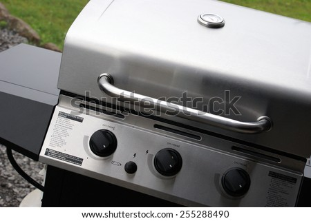 A brand new stainless steel bbq being used for the first time to welcome the summertime gatherings. - stock photo