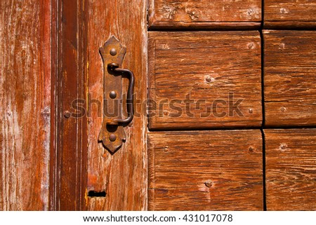 a brass brown knocker and wood  door cairate varese italy - stock photo