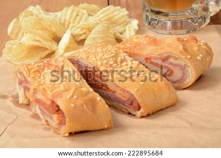 A bread roll stuffed with Italian meats and cheeses, with beer and potato chips - stock photo