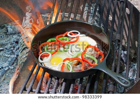 A breakfast of eggs on toast with bacon,onions and peppers frying on a grill at a state park.