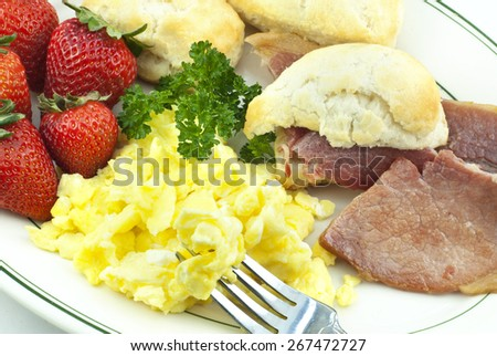 A breakfast plate filled with homemade country ham, scrambled eggs, fresh strawberries and biscuits, closeup