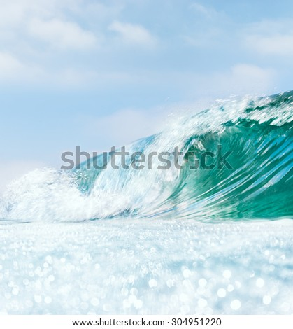 A breaking ocean wave with bright bokeh patterns in the foreground.  A somewhat slow shutter-speed was used for a partial blurring effect.