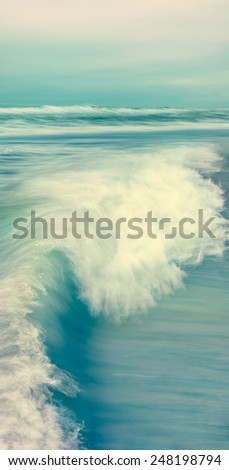 A breaking wave and stormy sea in a vertical panorama format.  Image made with blurred panning motion and cross-processed colors. - stock photo