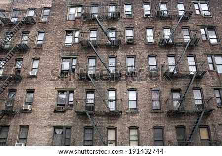 A brick apartment building in New York City with many windows and fire escapes - stock photo