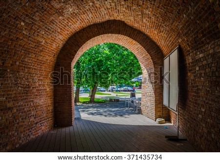 a brick arch with a green tree behind it.
