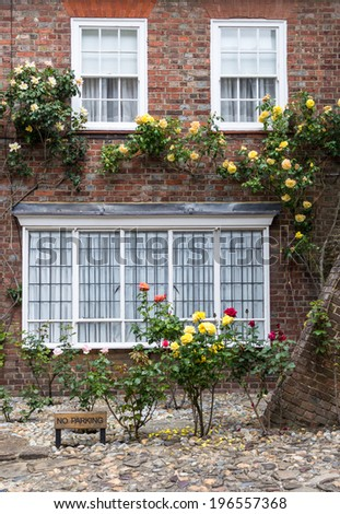 A brick house with roses on the front porch, seen in Rye, Kent, UK. - stock photo