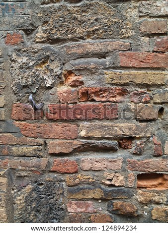 A brick wall with dents and holes in it - stock photo