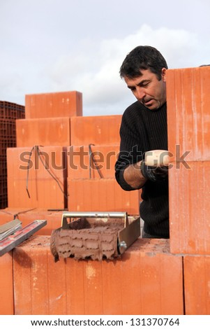 A bricklayer busy at work - stock photo