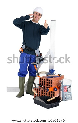 A bricklayer posing with his tools and building materials - stock photo