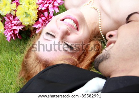 A bride and a groom lying on the grass, smiling