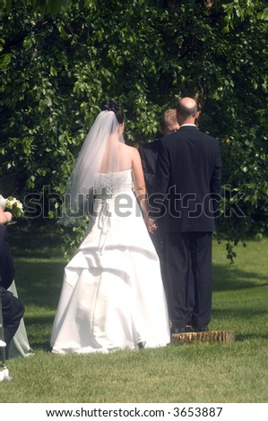 A bride and groom are married during an outdoor wedding ceremony