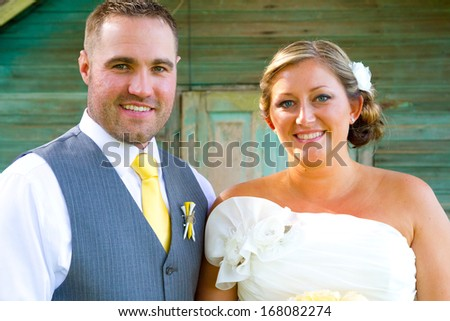A bride and groom looking beautiful and handsome on their wedding day outdoors for a portrait session. - stock photo