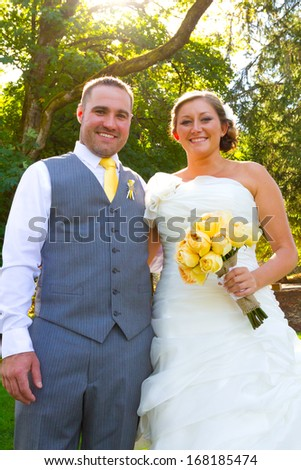 A bride and groom pose for a casual portrait on their wedding day outdoors in the summer in oregon. - stock photo