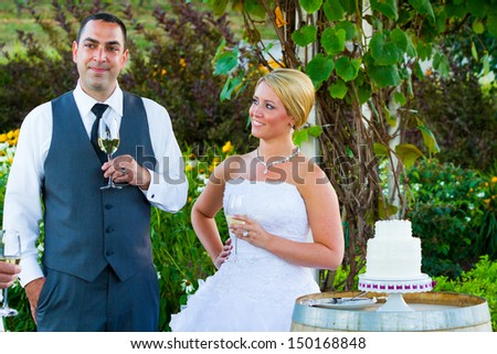 A bride and groom share a moment together while the best man and maid of honor toast them at their wedding reception.