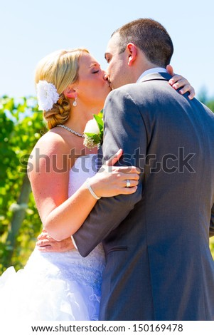 A bride and groom share a romantic kiss on their wedding day at a winery vineyard in oregon. - stock photo
