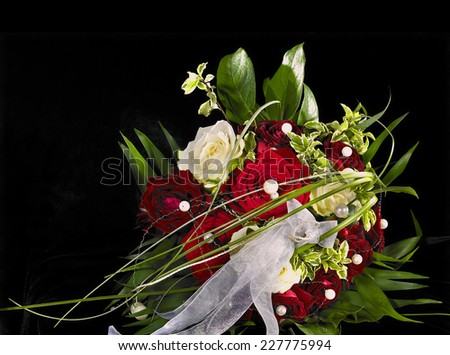 a bride bouquet with red and white rose flowers in black back - stock photo